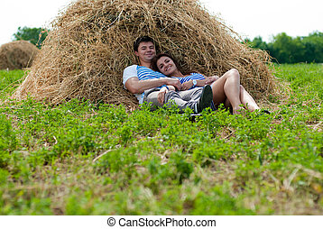 Happy young couple embracing resting on hay