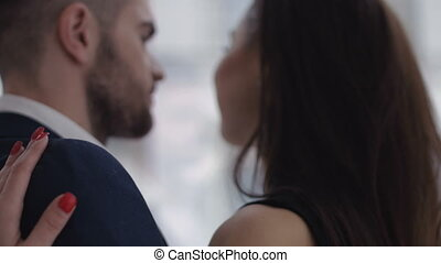 Happy young couple enjoying an intimate moment, laughing a lot and man gently strokes his partner's hair