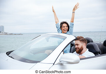 Happy young couple enjoying road trip in their convertible