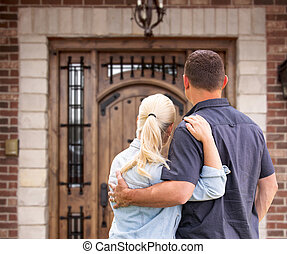 Happy Young Couple Facing Front Door of New House