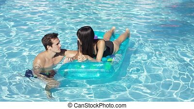 Happy young couple floating on mattress in pool