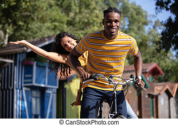 happy young couple going for a bike ride in city