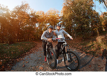 Happy young couple going for a bike ride on an autumn day in the park, backlight.