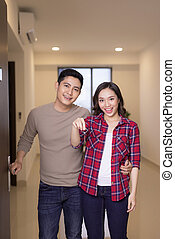 Happy young couple handing their new home keys and open house door