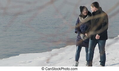 happy young couple has fun walking next to bank of river...