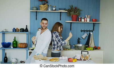 Happy young couple have fun dancing and singing in kitchen...