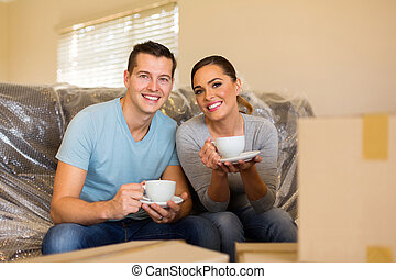 young couple having coffee break during moving