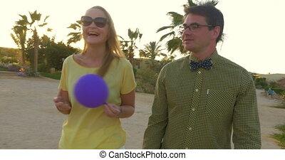 Happy young couple having enjoyable walk on tropical resort