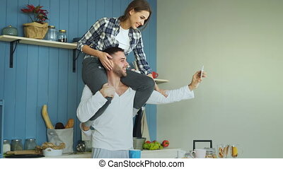 Happy young couple having fun and talking online video call...