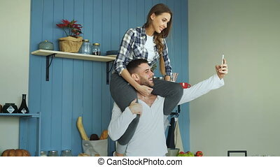 Happy young couple having fun in kitchen at home. Girl is...