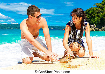 Happy young couple having fun on the shore of a tropical...