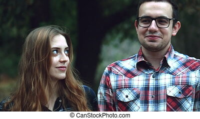 Happy young couple hipster, look at the camera and at each other during a summer walk in the park. 4k
