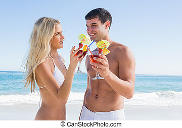 Happy young couple holding cocktails
