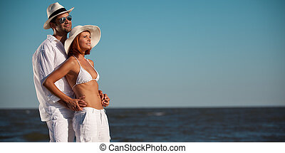 happy young couple holding each other seaside