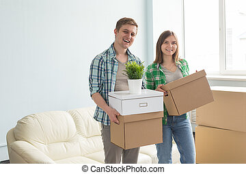 Happy young couple holding moving boxes with sofa on the background.