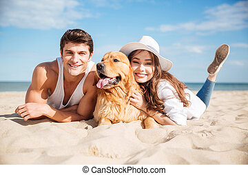 Happy young couple hugging with dog on the beach