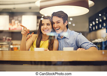 Happy young couple in cafe pointing to something