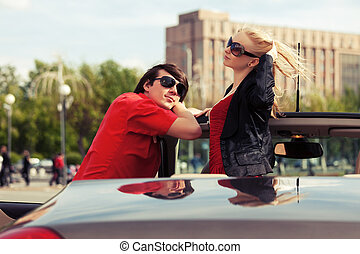 Happy young couple in convertible car
