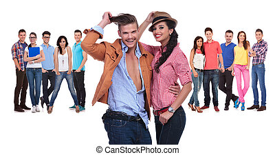 happy young couple in front of a large team of casual people