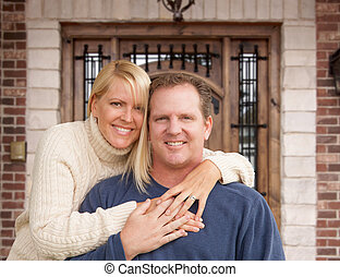 Happy Young Couple In Front of Front Door of House