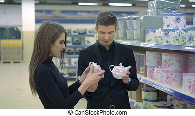 Happy young couple in furniture store choosing china cups and teapot