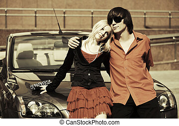 Happy young couple in love at the car