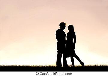 Happy Young Couple in Love Silhouetted Against Sunset in the Sky