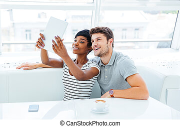 Happy young couple in love taking selfie with pc tablet