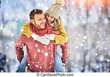 Happy Young Couple in Winter Park laughing and having fun. ...