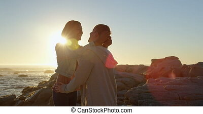 Happy young couple interacting with each other on rocky shore 4k