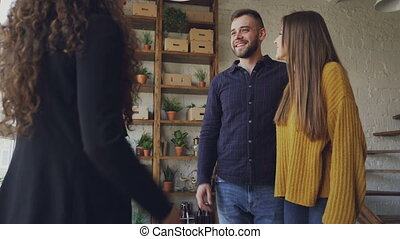 Happy young couple is buying new house shaking hands with...