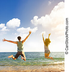 happy young couple jumping on the beach