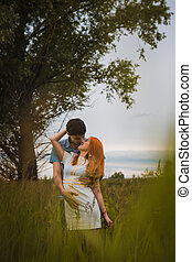 Happy young couple kissing on a ripe field