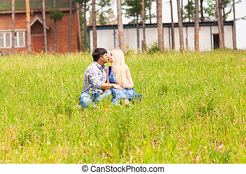 Happy young couple kissing on the lawn in a summer park. Love concept. Vacation.