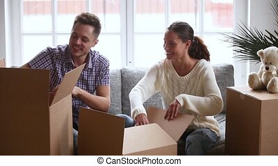 Happy young couple laughing talking unpacking open cardboard boxes together