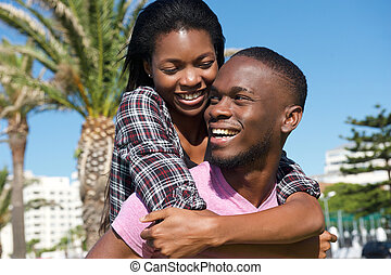 Happy young couple laughing together outdoors