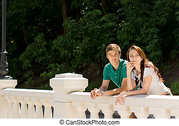 Happy young couple leaning on a balustrade