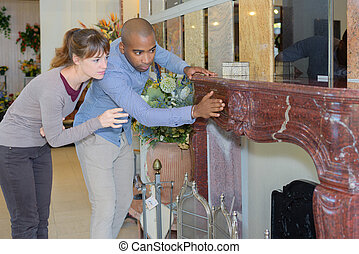 happy young couple looking at chimney in furniture store