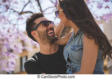 Happy young couple looking at each other laughing