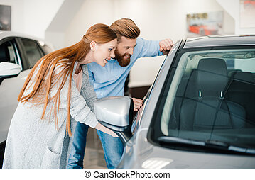 Happy young couple looking at new car in showroom