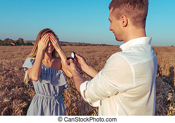Happy young couple love, summer wheat field. The girl closed her eyes. A man makes a wedding proposal marriage. Emotions happiness surprise, love, delight, surprise of care, joy, young family.