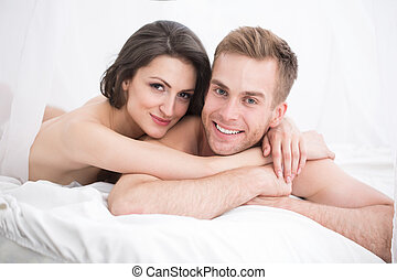 Happy young couple lying in white bed,