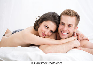 Happy young couple lying in white bed