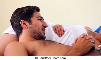 Happy young couple lying on a bed talking