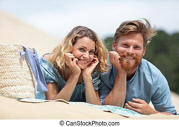 happy young couple lying on beach