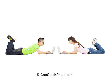 happy young couple lying together with laptop