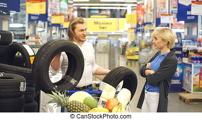 happy young couple make choice with car tires in shopping mall