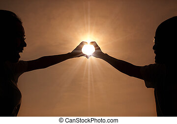 happy young couple making heart shape with hands  at sunset