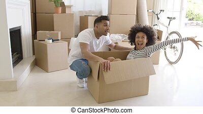 Happy young couple moving house together with the pretty...