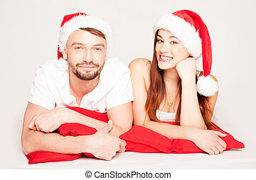 Happy young couple on a Christmas mood wearing Santa Hats and lying in the ground